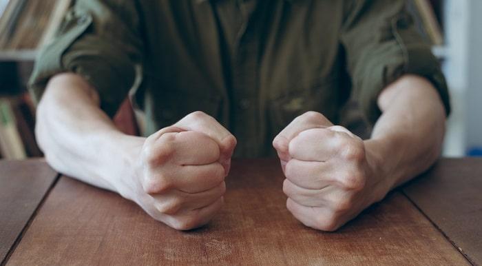 握りこぶしをつくり怒っている雰囲気を感じる男性