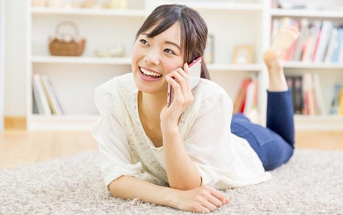 横になり電話をかける女性