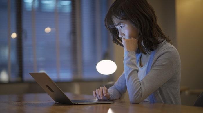 夜にパソコンで調べ物をする女性