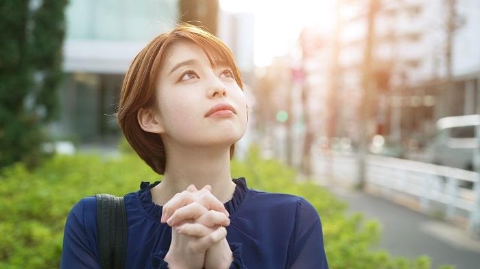 祈り空を見上げる若い女性