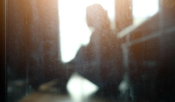 落ち込んで座り込む女性の影