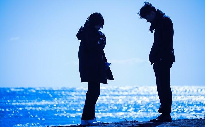 海辺で向かい合うカップル