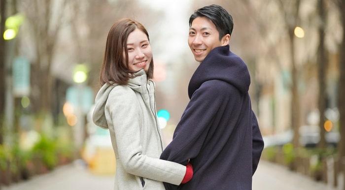 腕をくみ笑顔のカップル