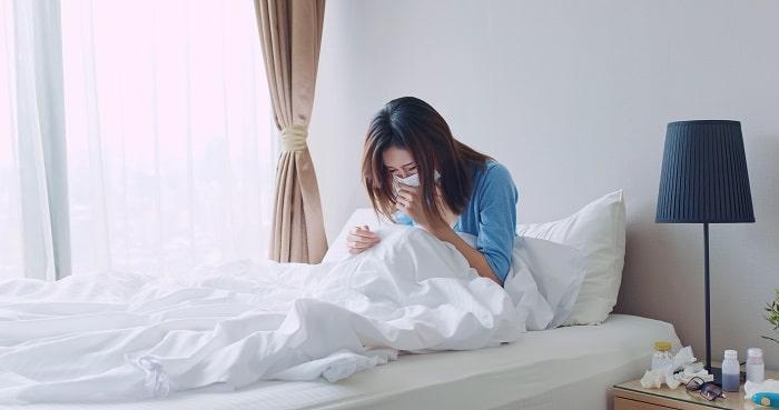 ベッドでせき込む女性