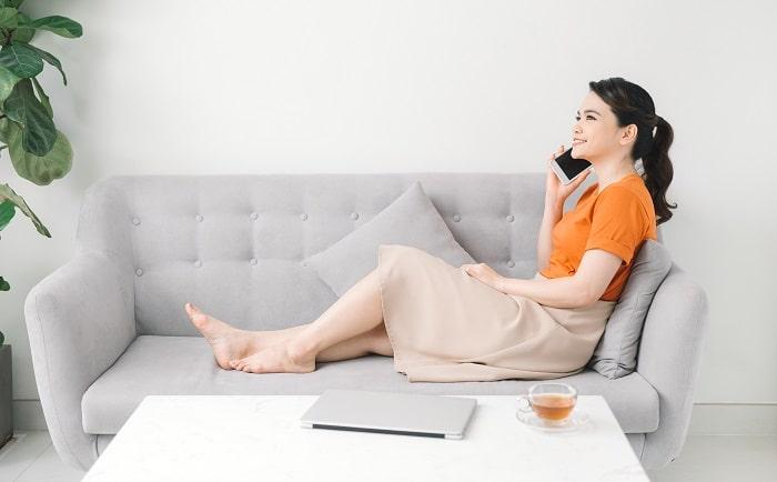 ソファで電話する女性