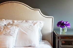 ベッドルームに置いてある枕とサイドテーブルに置いてある紫の花