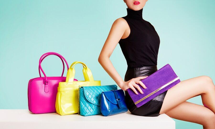 おしゃれな女性が紫の財布を持ち隣にカラフルなバッグを置いている