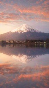 夕日で暗いオレンジ色に変化した雲に覆われる富士山を儚げに捉えた写真待受