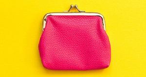 黄色いテーブルに置かれたピンク色のがま口財布