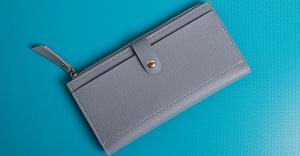 落ち着いたブルーのテーブルに置かれた灰色の合皮財布