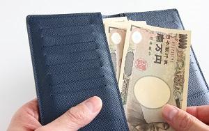 一万円札を財布に入れる