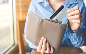 カードをグレーブラウンの長財布にしまう女性