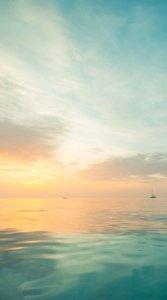 夕方日が暮れる時間の海と船を幻想的に写した待受