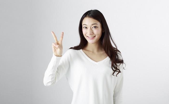 笑顔でvサインする若い女性
