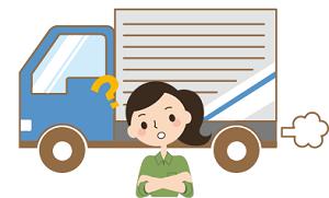 引越のトラックの前で考える女性
