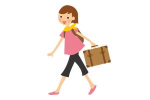 大きなバッグを持って旅行へ行こうとする女性