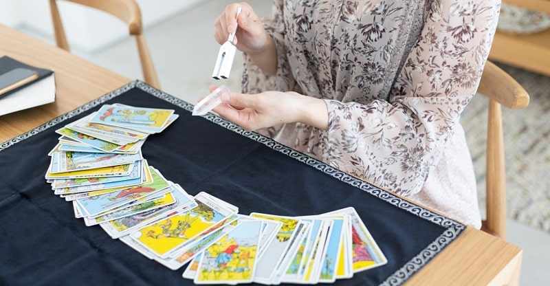 タロットカードの前で水晶を音叉で浄化する女性