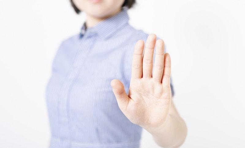 手を前に出してストップサインをしている女性