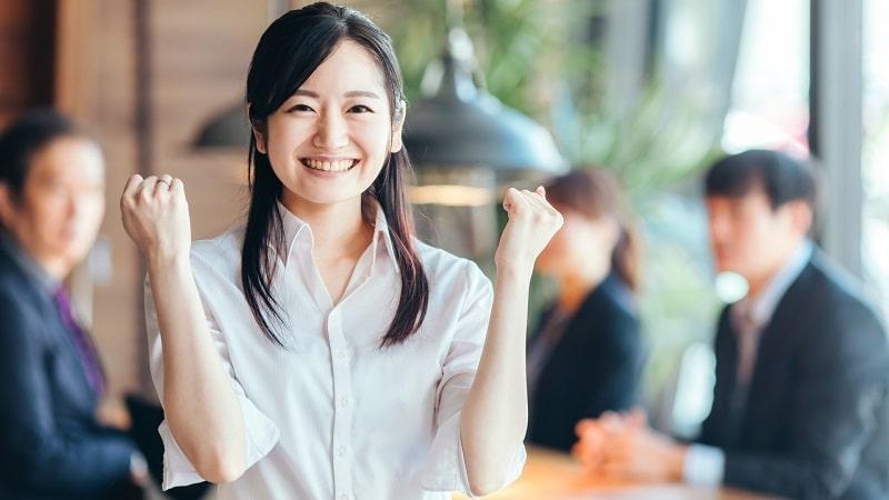 職場でガッツポーズをする女性