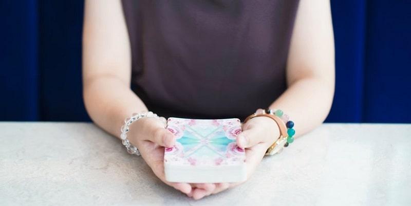 オラクルカードを両手で持つ女性