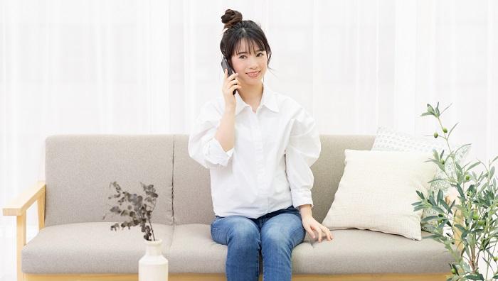 ソファに座って電話をしている女性