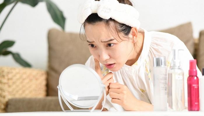 女性が鏡を見て肌の調子があまり良くないなと感じている様子