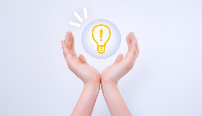 ひらめき・アイデアを想像させる電球の画像とそれをつつみこむ両手