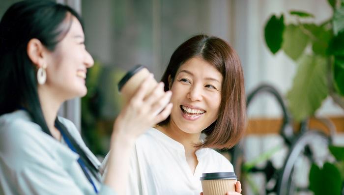 女性二人が飲み物を持ちながら笑顔で話をしている様子