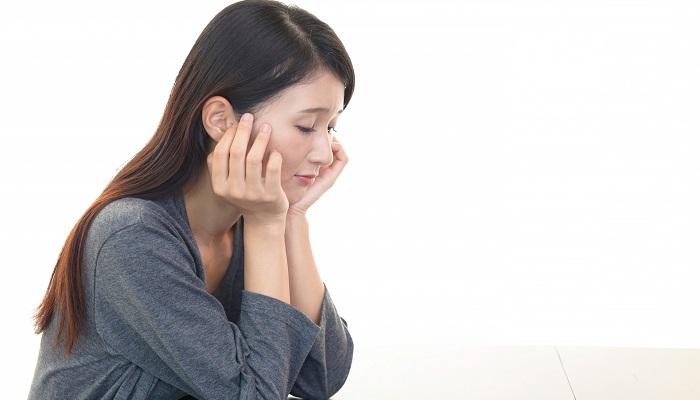 机にひじをついて考え事をしている女性